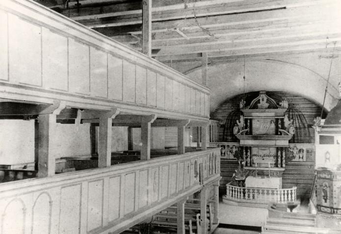 Øyestad kirkes interiør før brannen i 1900. Her sees altertavlen med skyggemalerier på tømmerveggen bak, samt prekestol med lydhimmel over. Dette gikk tapt i brannen. (Foto: Riksantikvarens billeddatabase, kulturminnebilder.ra.no.)