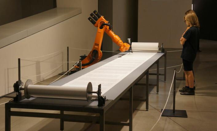 Roboten i Det jødiske museet i Berlin skriver Torah på en papirrull som er 80 meter lang.   (Foto: Arnfinn Christensen, forskning.no)