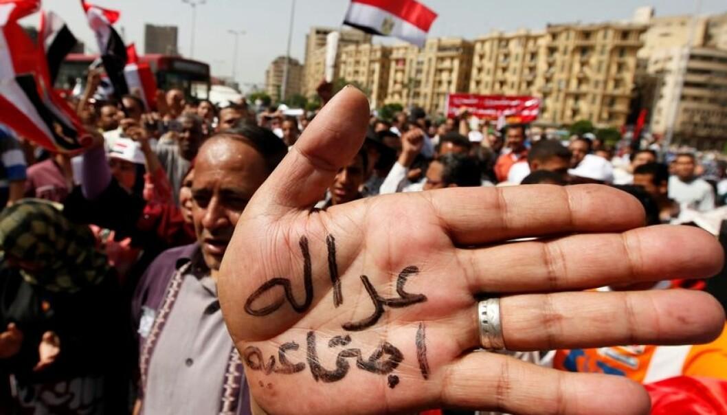 """Fra en demonstrasjon på arbeidernes dag i Kairo. Større politisk frihet i Egypt har også gitt fagforeninger større muligheter. I håndflaten står det """"sosial rettferdighet"""". Bildet er fra 1. mai 2011. (Foto: Reuters)"""