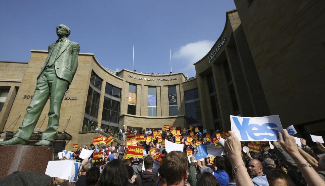 Folket har vært omtrent delt på midten før folkeavstemmingen. I dag faller dommen. Her fra et Nei-arrangement i Glasgow, som ble forsøkt avbrutt av Ja-supportere. Statuen er av Donald Dewar som var den første statsministeren i Skottland.   (Foto: Scanpix/Reuters, Paul Hacket)