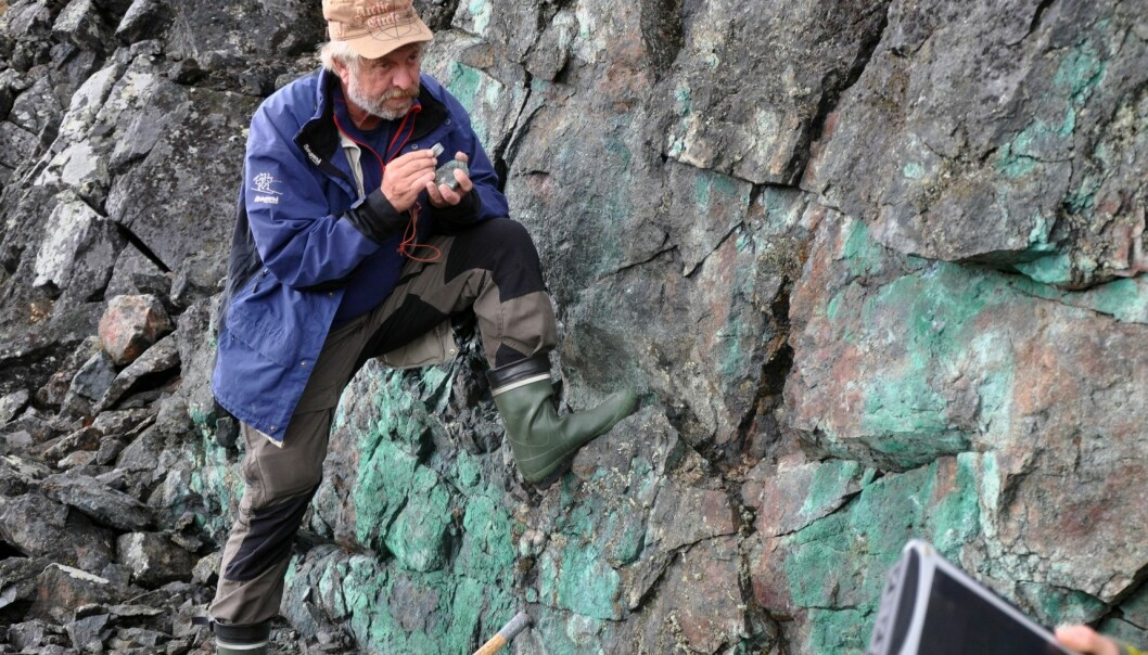 NGU-geolog Jan Sverre Sandstad studerer en kobberforekomst ved Porsvann. Grønnfargen utenpå bergarten forteller at det er mye kobber i berget.  (Foto: Magne Vik Bjørkøy, NGU)