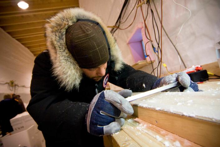 Arbeid i NEEM-leir på Grønland: Postdoktor Vasileios Gkinis renser en nyskåret iskjerne. (Foto: Senter for is og klima)