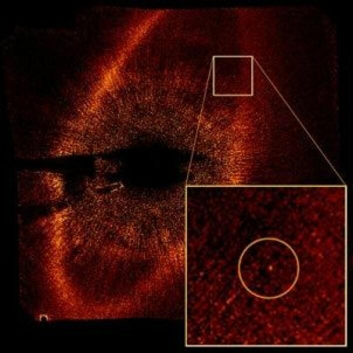Romteleskopet Hubble har tatt et bilde som viser et belte av støv og klumper (den lyse ovalen) rundt stjerna Fomalhaut. Planeten (uthevet) feier veien innenor dette støvbeltet. En koronograf blokkerer ut lyset fra stjerna i midten, som er 100 millioner ganger lysere enn planeten. (Foto:Paul Kalas/UC Berkeley, NASA, ESA)