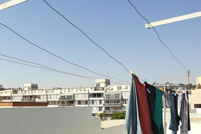 Når jeg vet hva jeg skal se etter så ser jeg at de øverste vinduene på bygget er mye mindre enn vinduene på leilighetene i etasjene under. I øverste etasje bor hushjelpene som jobber for de som bor i leilighetene under. Dette leilighetskomplekset ble mest sannsynlig bygget under apartheid. De sosiale og politiske strukturene på den tiden kommer til uttrykk i arkitekturen selv i dag. (Foto: Oda Maiken Maraire)