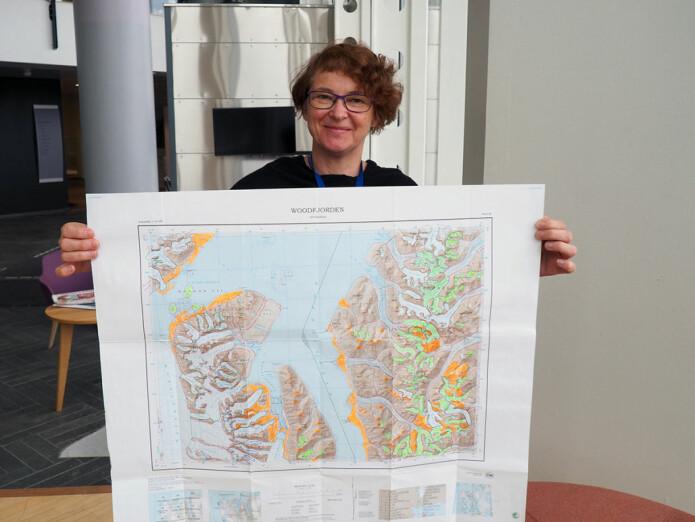 Leiar av namnekomiteen, kartograf Oddveig Ørvoll, viser frem eit av karta som har fått nye stadnamn. Dei aktuelle områda er merkt av med fargar på karta. Dei grøne felta viser isbrear, medan dei oransje er land- og fjellområde. (Foto: Elin Vinje Jenssen / Norsk Polarinstitutt)