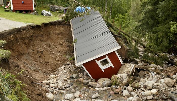 I August 2013 førte store nedbørsmengder til flom og oversvømmelse i Brumunddal. Veien ble vasket bort i Spikdalsveien og her ser vi at et uthus ble tatt av vannmassene. Foto: Cornelius Poppe / NTB scanpix