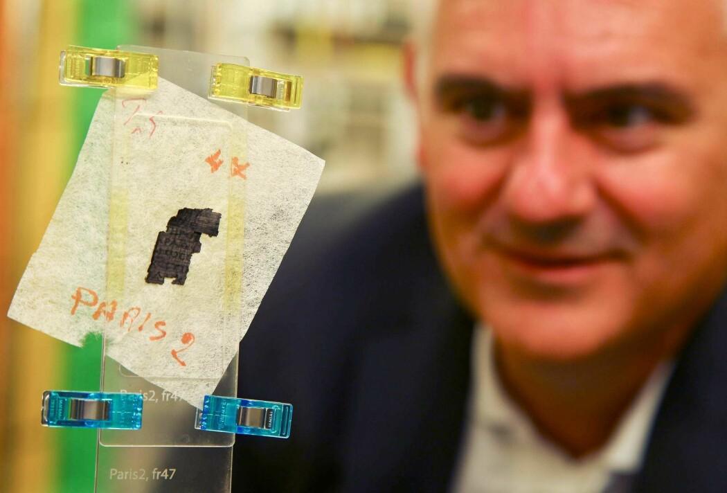 Her ser du forsker Brent Seales med en bit papyrus som akkurat har blitt scannet. Han og kollegaene håper nå at kunstig intelligens kan hjelpe med å avsløre innholdet i forkullede ruller fra Herculaneum og Pompeii. (Foto: Geoff Caddick, AFP, NTB Scanpix)