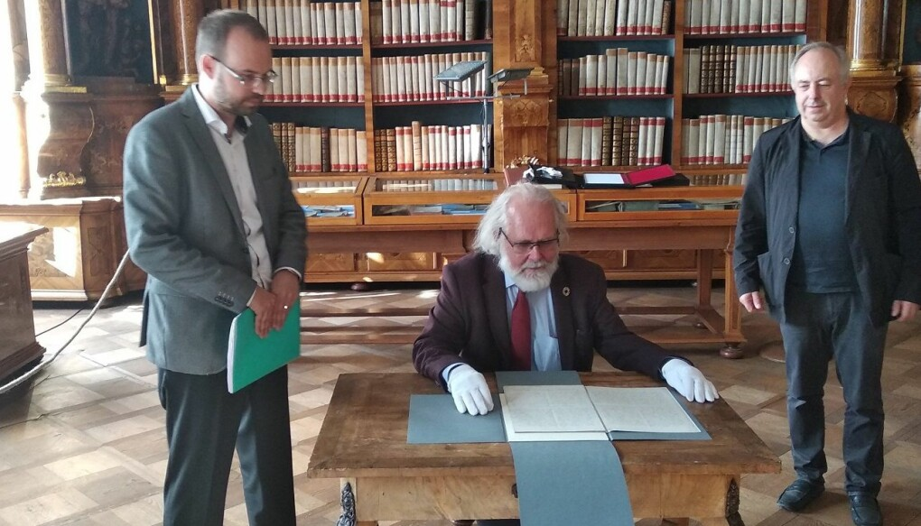 Professor Nils Chr. Stenseth blar andektig i Gregor Mendels håndskrevne originalmanuskript fra 1865. (Foto: Ellen Repiková, Společně.org).
