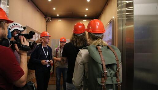 Journalistene går, uten å nøle, inn i heisen som skal frakte dem 100 meter under bakken. (Foto: Lasse Biørnstad)
