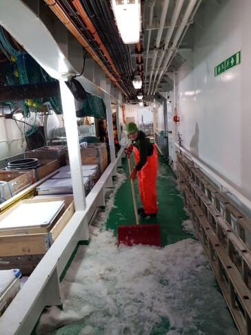 Det snødde og akterdekket og utstyret ble nediset – Jossan ordner opp med «snøskrapen». (Foto: Andrey Voronkov)