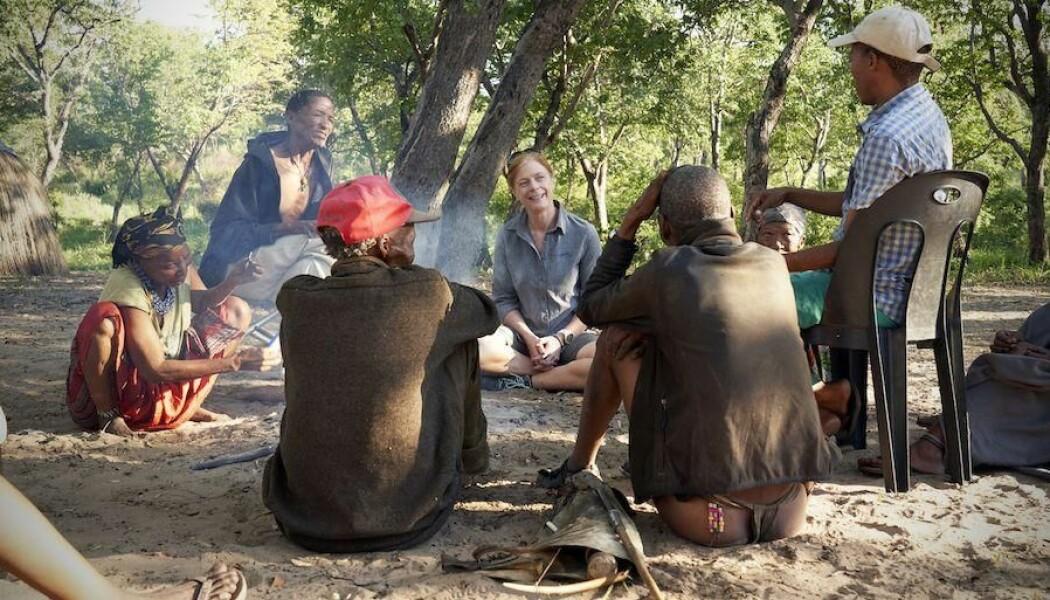 Vanessa M. Hayes i samtale med lokale Juǀ'hoansi-jegere i Kalahari i Namibia. De skal lære henne å gjøre opp ild. (Foto: Chris Bennett, Evolving Picture)