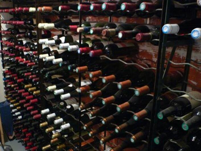 Marcel har 200 flasker i sin vinkjeller, men hyllene har huller etterhvert som vinen konsumeres. De er sortert etter farge og område, men årganger ligger hulter til bulter. Han synes det får holde å rydde et par ganger i året. (Foto: Delphine Deon)