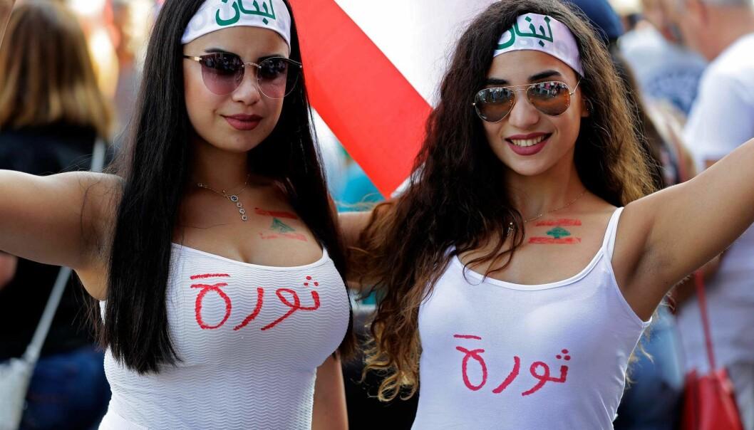 I Beirut demonstrerer to ungdommer med ordet «revolusjon» skrevet på T-skjortene. De vil bli kvitt den politiske eliten i Libanon som i årtier har sittet med makten. (Foto: Joseph Eid/ AFP/scanpix)
