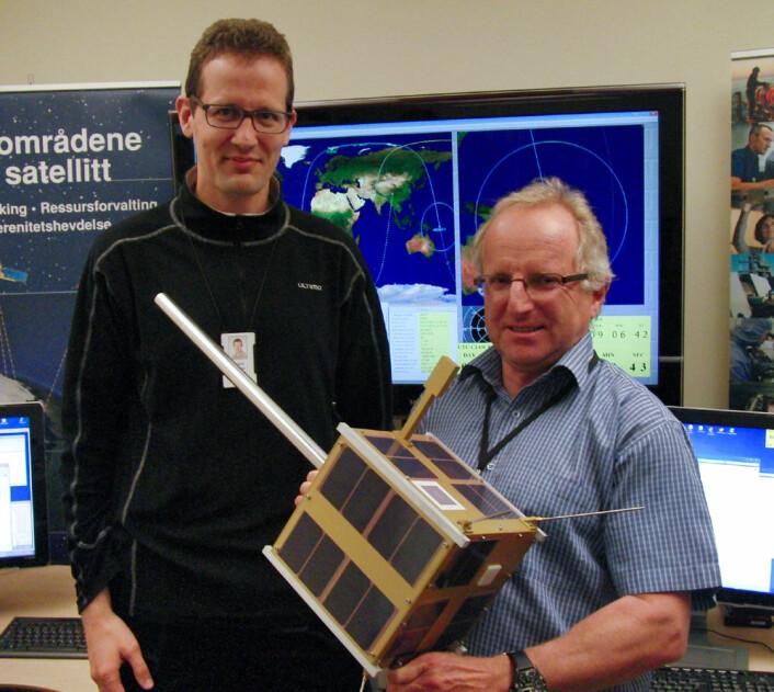 Øystein Helleren (t.v.) og Richard B. Olsen med fullskalamodell av AISSat-1 i kontrollrommet på Forsvarets Forskningsinstitutt der signalene fra satellitten overvåkes. Satellitten måler 20x20x20 cm, og stangen som stikker ut er antennen som tar imot signaler fra skip. (Foto: Arnfinn Christensen, forskning.no)
