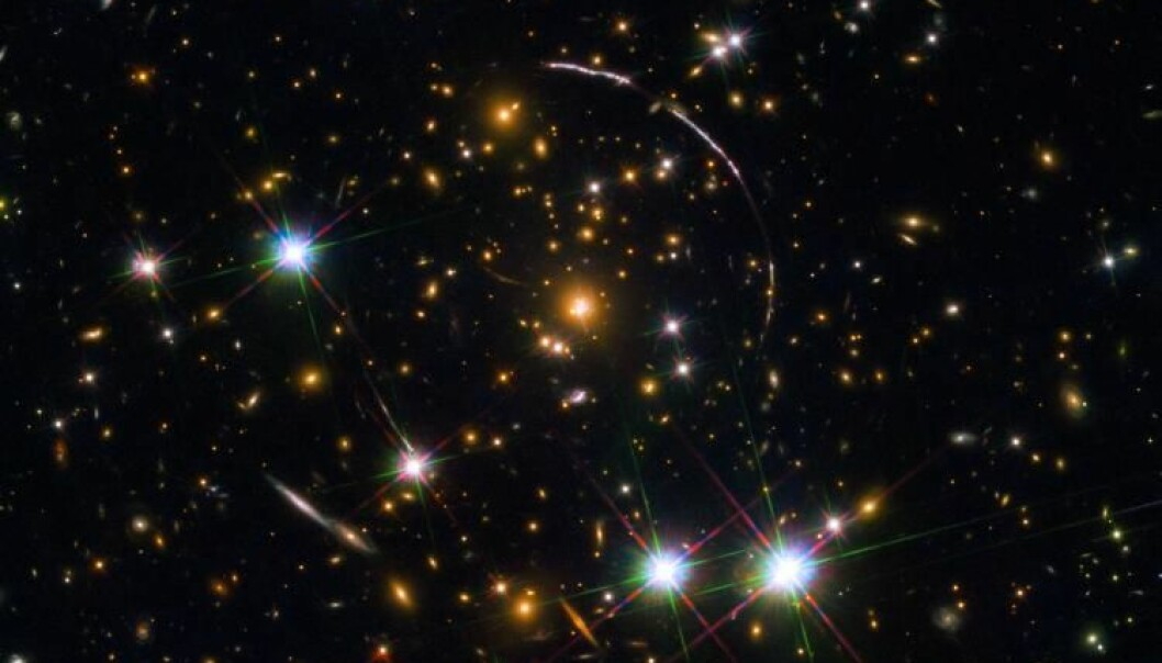 A Hubble Space Telescope photo of a massive galaxy cluster, about 4.6 billion light years away. Along its borders four bright arcs are visible; these are copies of the same distant galaxy, nicknamed the Sunburst Arc Galaxy. Photo: ESA/NASA/Rivera-Thorsen
