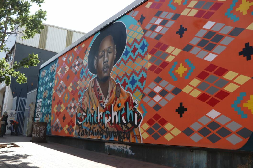 Dette veggmaleriet er en reklame for artisten Samthing Soweto sitt nye album 'Isphithiphithi'. På siden er det lagt ved en QR-kode som gjør at forbipasserende med et tastetrykk finner musikken. Denne måten å bruke offentlig rom viser også hvordan flere sanselige medium kommer sammen og hvordan kunstneriske og kommersielle interesser overlapper. (Foto: OEM, Oktober 2019)