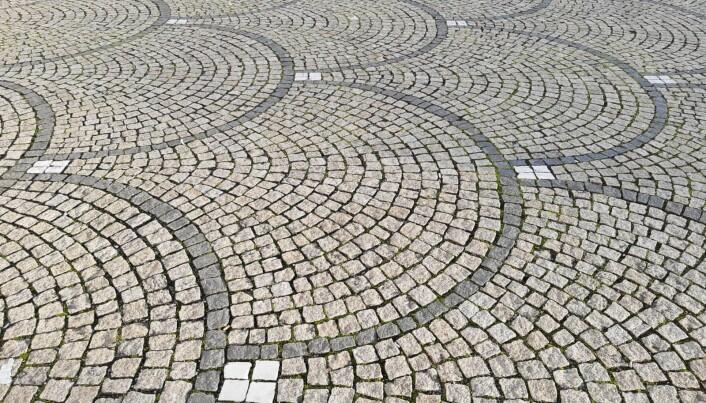 Brosteinsanlegg på Königsplatz med mønster av mørk basalt, lys granitt og hvit marmor.