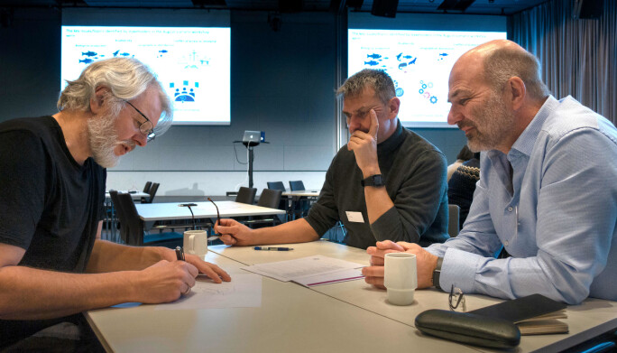 Oseanograf Arild Sundfjord (t.v.) tegner og forteller hvordan havstrømmene går. Marinbiologene Ulf Lindstrøm og Børge Damsgård lytter og lærer.
