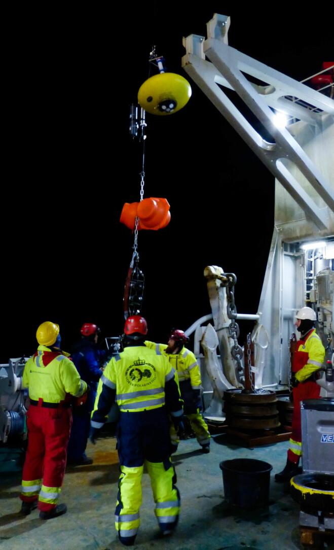 En instrumentrigg heves over ripa av personell fra Norsk Polarinstitutt og Havforskningsinstituttet. Måleinstrumenter montert på denne riggen skal gi informasjon om bl.a. istykkelse, havstrømmer, temperatur og saltinnhold. (Bilde: Øyvind Lundsgaard)
