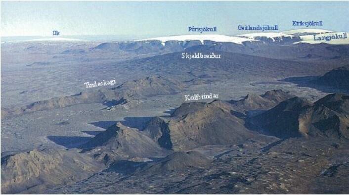 Figur 3: Utsikt mot nordvest, på skrå over den vestlige riftsonen. De bratte ryggformete fjellene i forgrunnen er dannet ved subglasiale utbrudd i den siste delen av siste istid. Riftsonebunnen mellom ryggene er dekket av lavastrømmer som jevner ut landskapet. Skjoldvulkanen Skjaldbreiður bak ryggene er dannet i ett sammenhengende, og voluminøst utbrudd av lava like etter isavsmeltingen. I bakgrunnen sees flere isdekte bordfjell i utkanten av den store isbreen Langjökull. Skjoldvulkanen Ok efra siste mellomistid er også synlig. Klikk her for større versjon. (Foto: Kristján Sæmundsson)