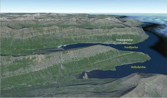 """Figur 7. Utsikt mot nord ved Neskaupstaður, lengst øst i Island. Dype fjorder og daler er skåret inn i de """"høyt-flytende"""" Tertiære lavaplatåene. På grunn av den omfattende innskjæringen av de øvre to km har skorpeplaten lav tetthet. Glasiale erosjonsformer med botner og rygger er lett synlige nederst til høyre. Lavastrømenhetene heller svakt i vestlig retning mot den Nordlige riftsonen utenfor bildeutsnittet. Helningen skyldes nedbøyning av skorpen som følge av innsynkning av den vulkanske lasten som pålagres i riftsonene. Klikk her for større versjon. (Foto: Google Earth)"""