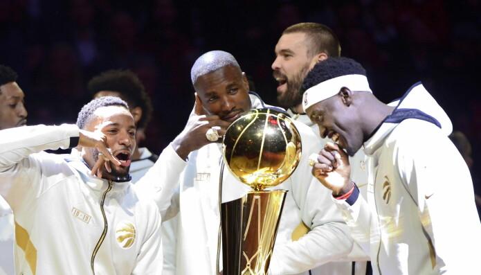 Basketspillere fra laget Toronto Raptors ser blide ut når de står rundt NBA-pokalen før den avgjørende kampen mot the Golden State Warriors.