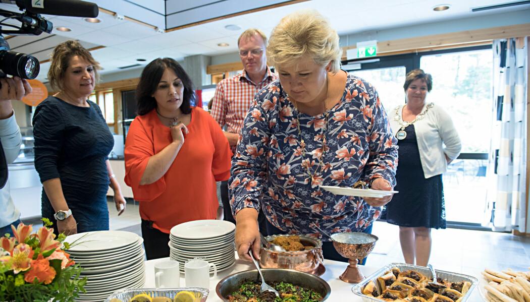 Dette bildet fra 2017 illustrerer arbeidsrettet integrering. Det er tatt i Fjell kommune som prioriterer integrering av flyktninger. I kantinen på rådhuset har de praksisplasser for flyktninger. Her serverer Shahnaz Fadaie (tv) og Paruin Joma internasjonal mat til statsminister Erna Solberg.