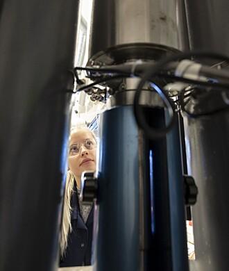 Master of Science, Laura Edvardsen, setter en sandsteinsprøve inn i maskina. Her skal den få prøvd styrken sin – med krefter fra alle hold.