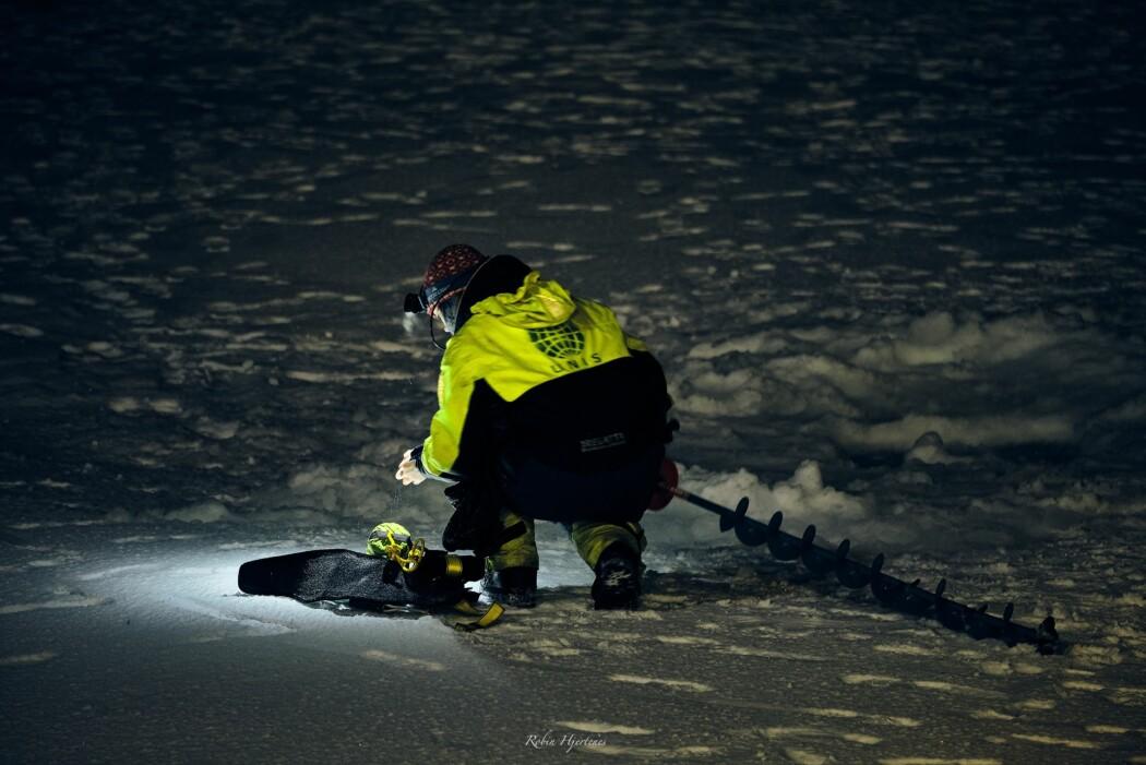 En forsker i gang med å ta en iskjerne opp fra havisen.
