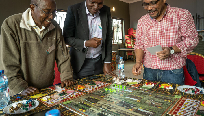Players stand around a game board as it is being set up.