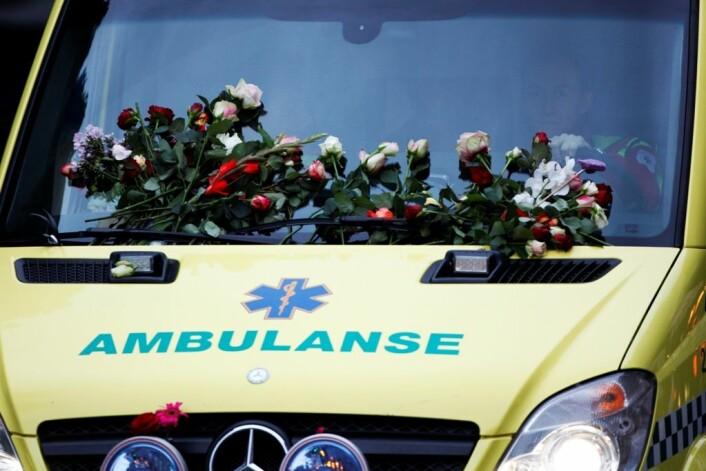 Ambulanse dekket med blomster. Over ett hundre tusen mennesker tok til gatene i Oslo for å vise støtte og omsorg for de omkomne etter bomben i regjeringskvartalet og i massakren på Utøya. (Foto: Trond Reidar Teigen / Scanpix)
