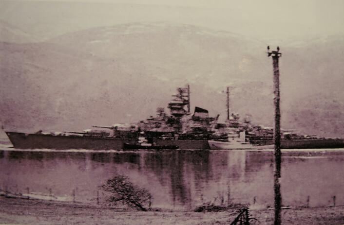 Tirpiz under slep gjennom , fotografert 16. oktober 1944 av telegrafist Arnold Lindsett kl. 12:45 fra vinduet mot Sandnessundet i vest. Dette er det siste bildet av der tyske slagskipet før engelske fly bombet det i senk to dager senere. (Foto: Norsk telemuseum, avdeling Tromsø)