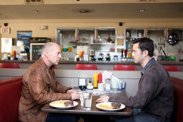 Bruce Willis sin rollefigur møter en yngre versjon av seg selv, spilt av Joseph Gordon-Levitt i filmen Looper. (Foto: Norsk Filmdistribusjon)