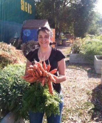 Fornøyd selvdyrker ved People's Portable Garden, med en bunt gulrøtter. (Foto: Wasatch Community Gardens)