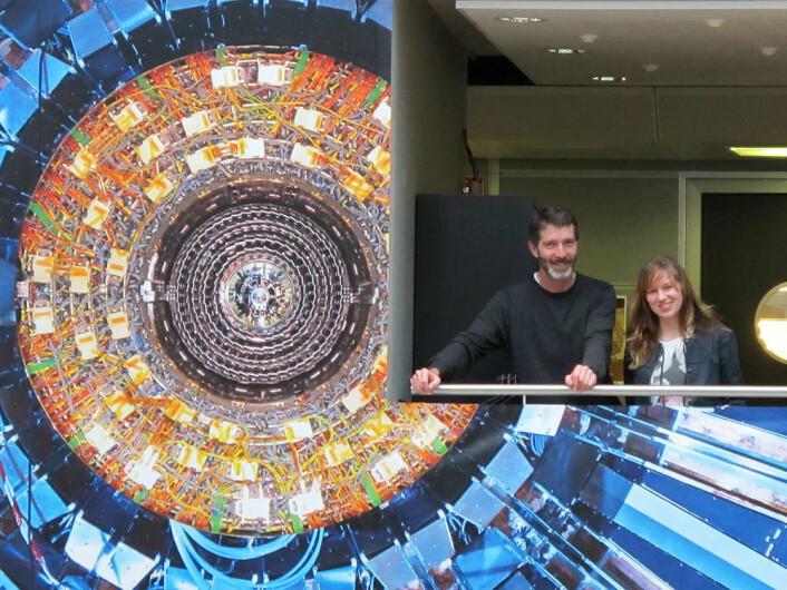 Higgs-jegerne Alex Read og Lillian Smestad ved en dekorert vegg i CERN-laboratoriet. (Foto: UiO)