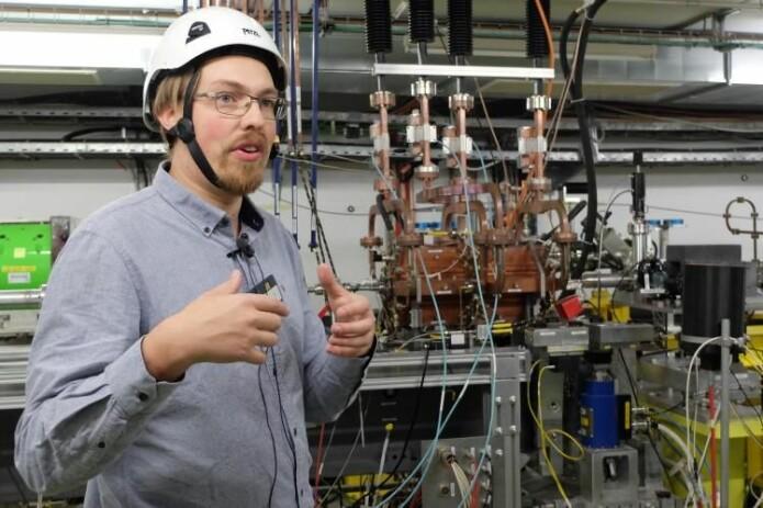 Kyrre Ness Sjøbæk forklarer hvordan han holder partikkelstrålen i sentrum ved hjelp av kobberinstallasjonen i bakgrunnen.