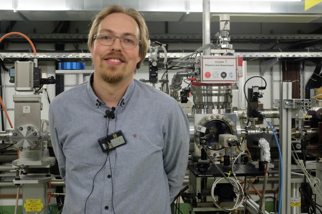 Kyrre Ness Sjøbæk på Clear-laboratoriet på Cern. I bakgrunnen plasmalinsen som skal fokusere partikkelstrålen.