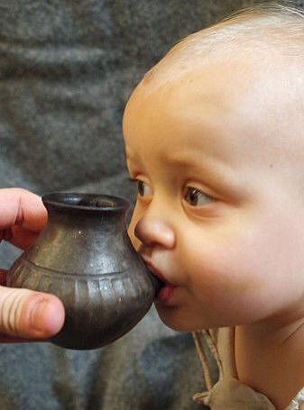 Her får en moderne baby drikke fra en kopi av en tutekopp.