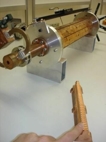 """""""Sylinderen i bakgrunnen er en PETS. Inni sitter kobberplatene med riller (som den i forgrunnen), som skreller elektronenes elektromagnetiske felt. (Foto: Espen Eggen)"""""""