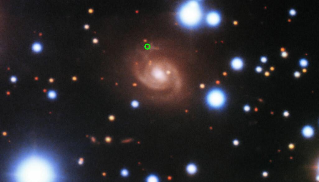 De gjentakende radioglimtene kom fra galaksen i midten. Den grønne sirkelen viser hvor.
