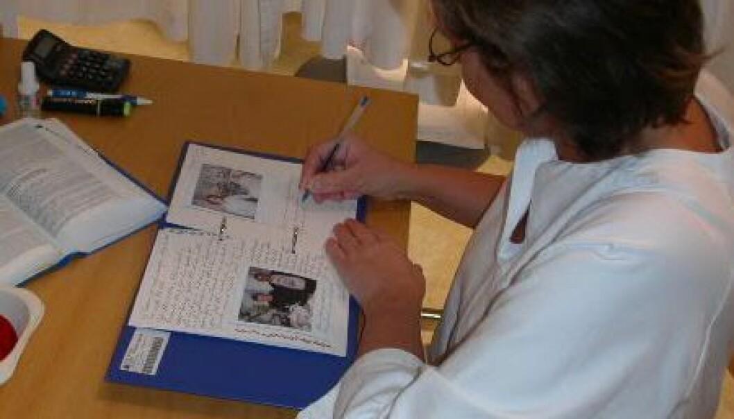 En sykepleier jobber med dagboken til en pasient på intensiven. Boken får pasienten når han eller hun skrives ut av avdelingen. (Foto: Sissel Lisa Storli)