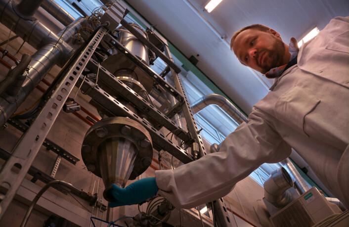 Forsker og områdeleder Werner Filtvedt henter ut silisumpulver fra Freespace-reaktoren som er utviklet ved Institutt for energiteknikk på Kjeller. (Foto: Arnfinn Christensen, forskning.no.)