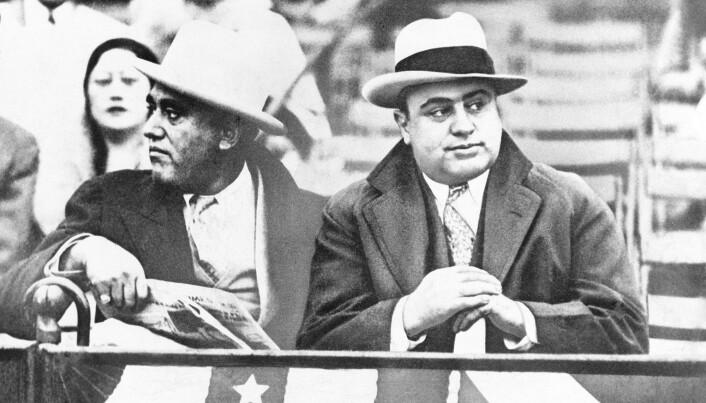 Gangsteren Al Capone (t.h.) på en amerikansk fotballkamp i Chicago. Al Capone tjente millioner av dollar på ulovlig spritsalg.