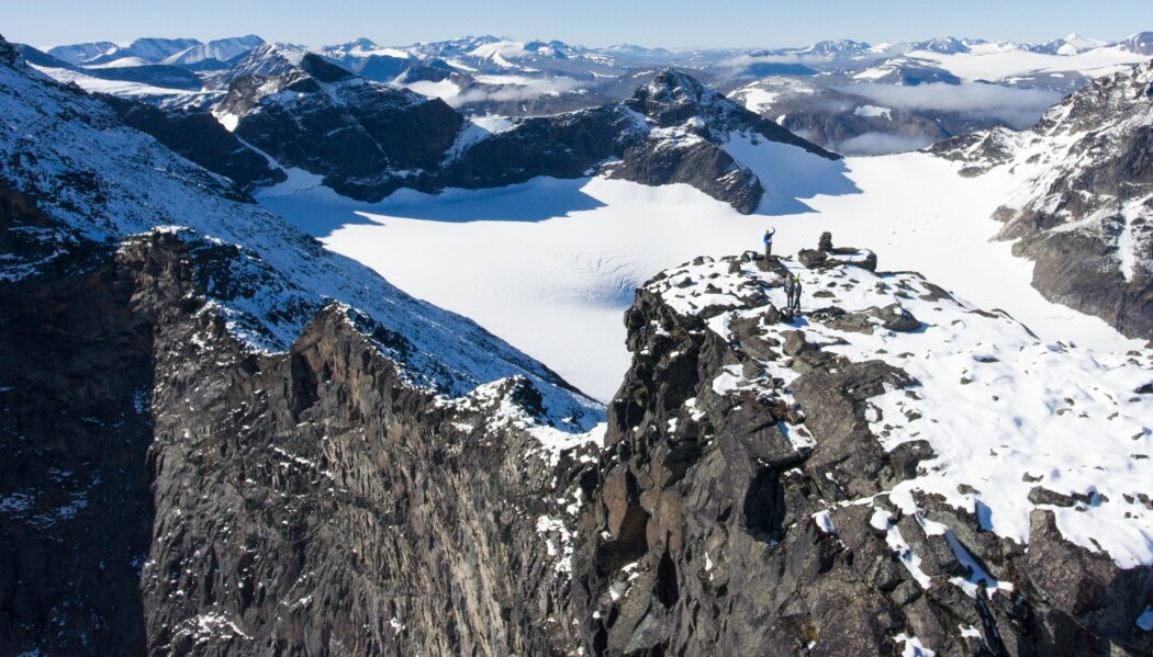 Fra en av toppene av Ähpar-massivet vinker Hans Jørgen Kjøll til helikopteret. Også her ligger mørke striper med lavastein på tvers i fjellveggen.