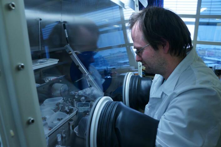 Seniorforsker Jan Petter Mæhlen arbeider med nanopulver av silisium i et skap fylt av edelgass, for å hindre uønskede kjemiske reaksjoner mellom silisium og luft. (Foto: Arnfinn Christensen, forskning.no.)