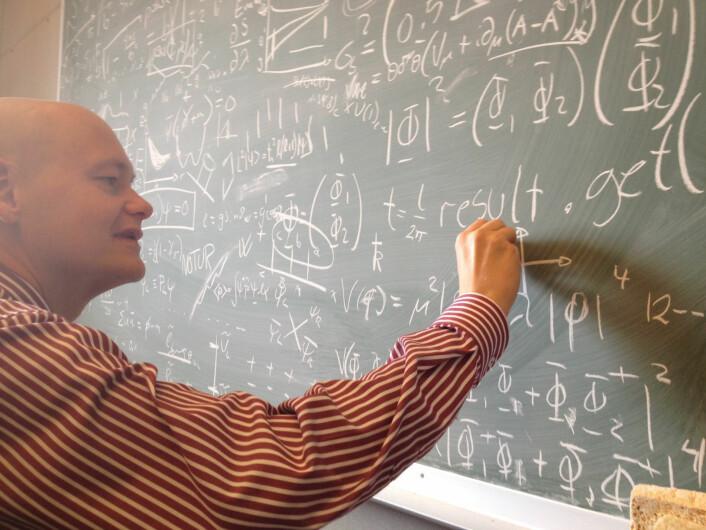 Professor Are Raklev ved Fysisk institutt, Universitetet i Oslo tegner på tavla på kontoret sitt. (Foto: Ingrid Spilde)