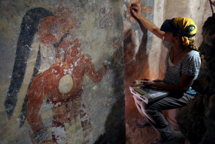 Konservator Angelyn Bass renser go stabiliserer overflata av veggen i mayahuset. Figuren til venstre kan forestille mannen som holdt til i huset. Kanskje var han byens skriver? (Foto: Tyrone Turner/National Geographic)