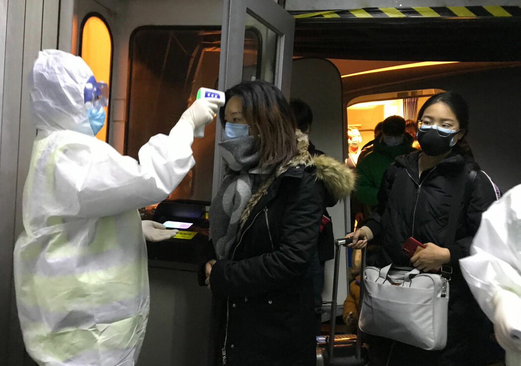 Helsearbeidere ved flyplassen i Beijing sjekker kroppstemperaturen til passasjerer fra Wuhan. 571 mennesker skal ha blitt smittet av det nye coronaviruset.