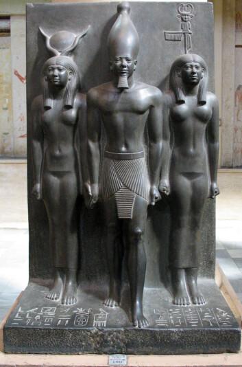 Menkaure, avbildet med gudinnen Hathor (t.h.) og en kvinnelig fremstilling av byen Diospolis Parva til venstre. (Foto: Wikimedia Creative Commons)