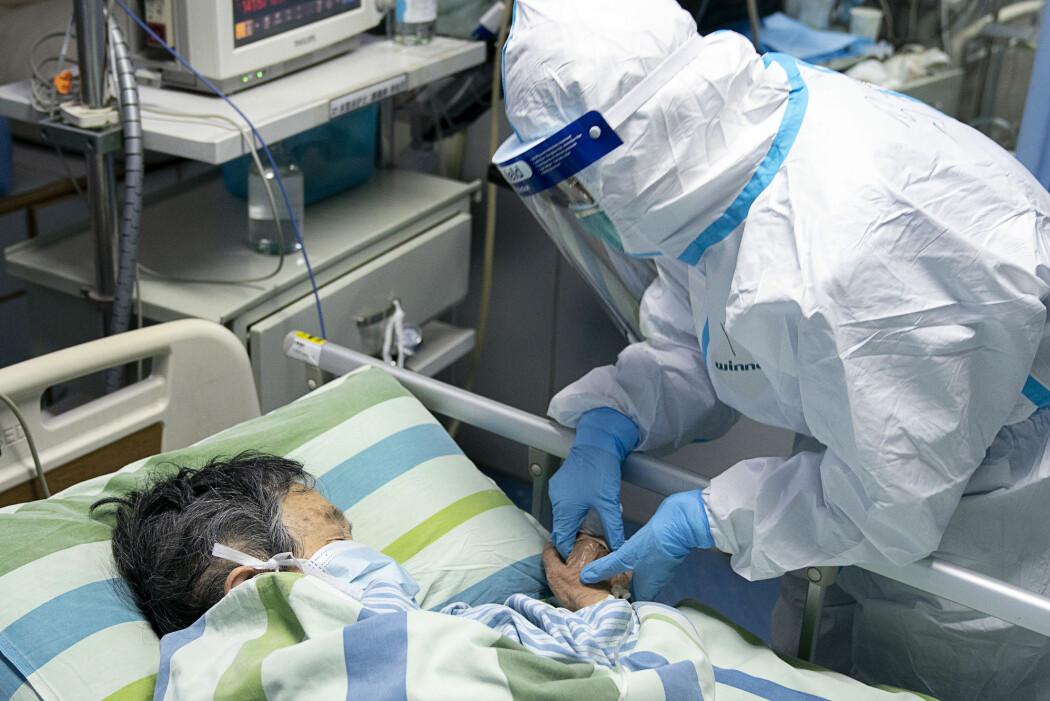 En helsearbeider ser til en innlagt på et sykehus i Wuhan, byen hvor virusutbruddet har rammet hardest.